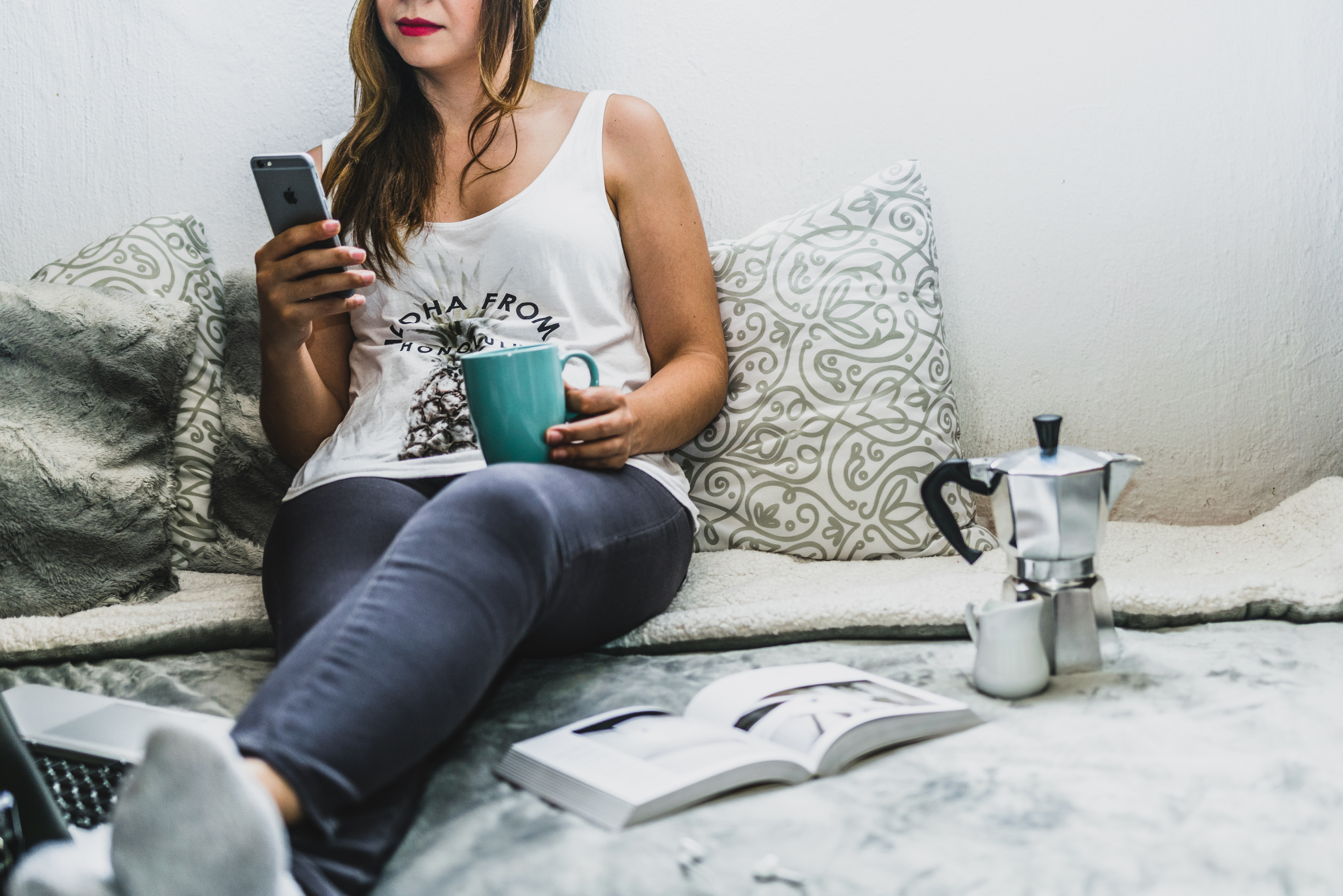 Woman sitting on bed with coffee browsing phone.