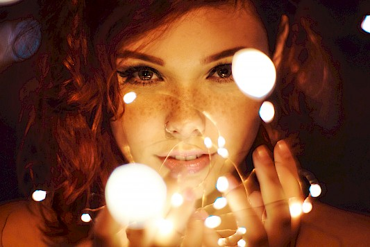Woman's face behind small circles of bright light.