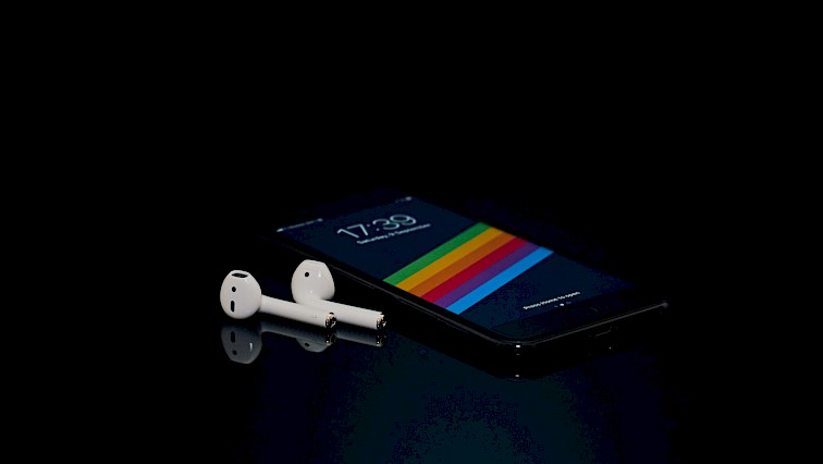 iPhone on black surface with wireless headphones
