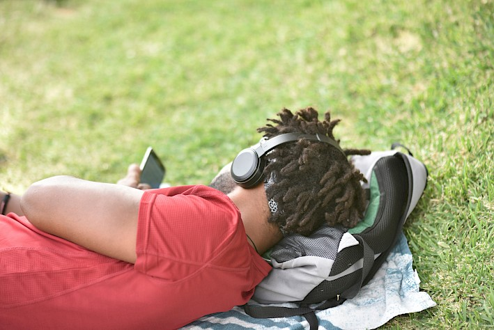 man watching a movie on his phone in the park