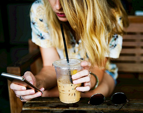 Woman drinking coffee while scrolling through phone