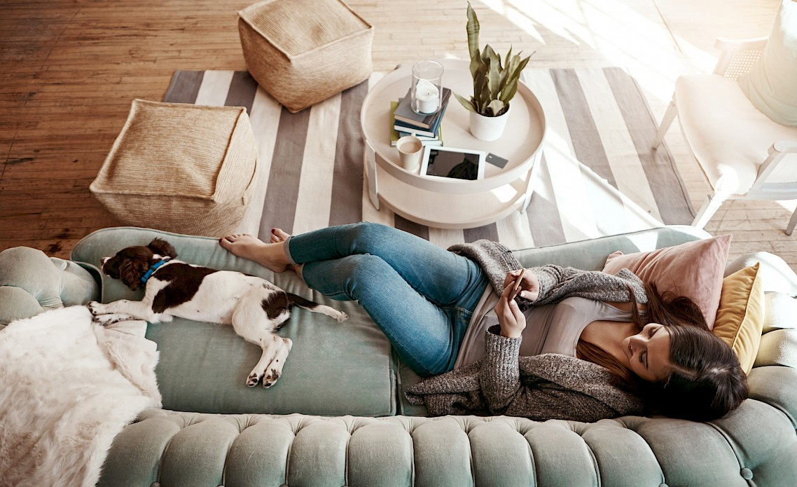 Woman using her phone and relaxing on couch with dog.
