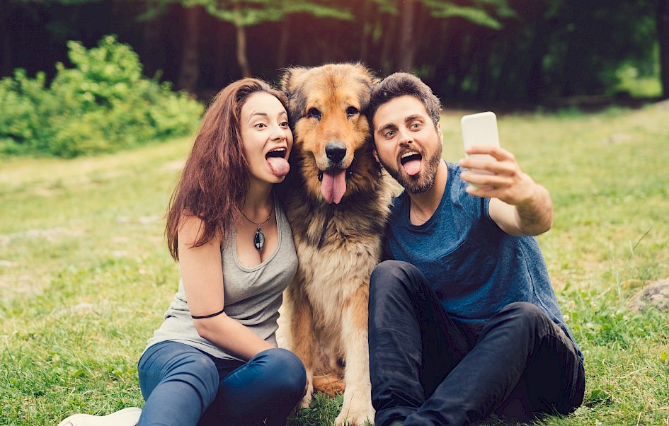 Couple takes selfie with dog outside