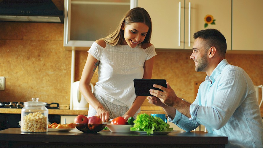 Couple cooks while checking directions on tablet