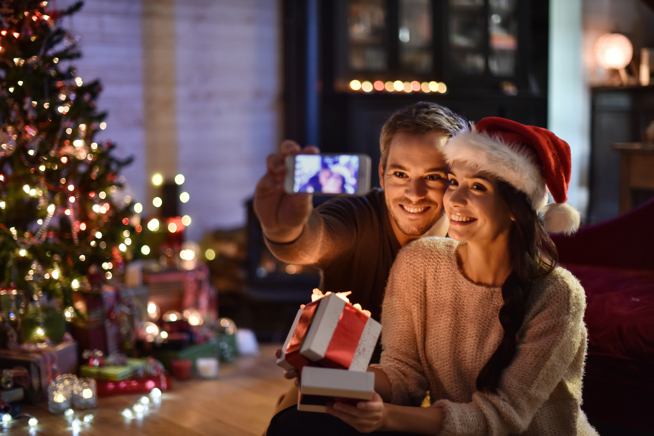 Couple opens gifts on Christmas Eve and takes selfie with new smartphone