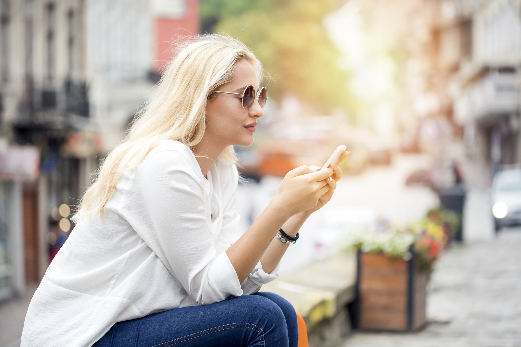 Young woman smiling with smartphone in hand
