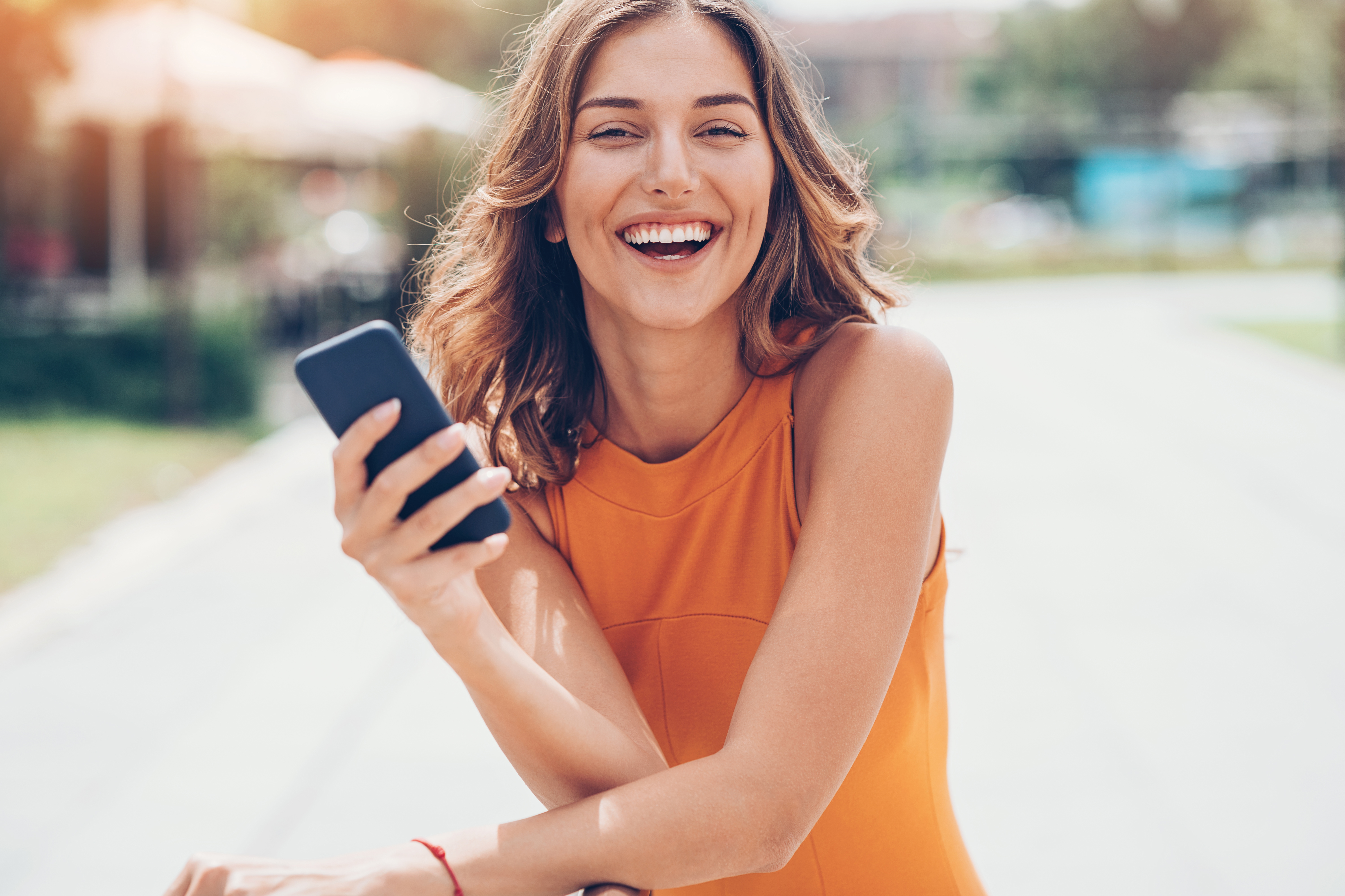 Woman laughing outdoors with phone in hand.